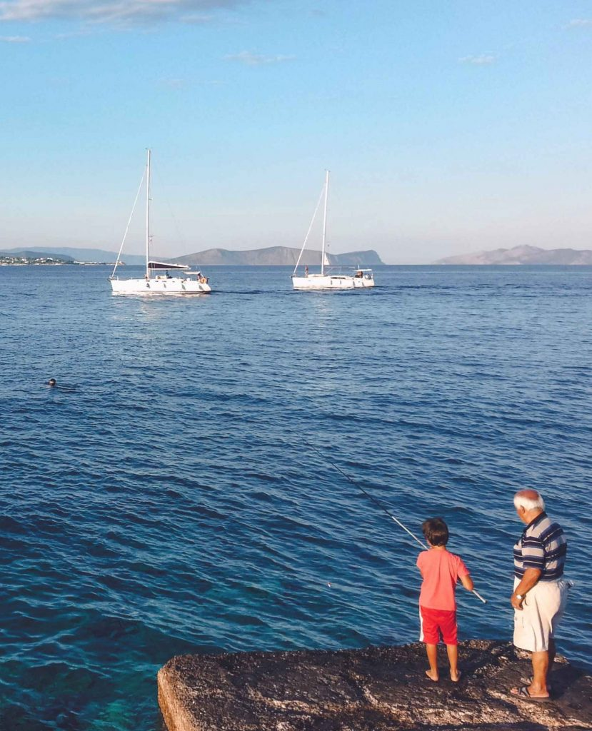 Un bambino e suo nonno pescano sull'isola greca di Spetses