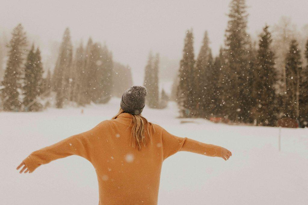 una ragazza con cappello e maglione in mezzo alla neve durante una nevicata