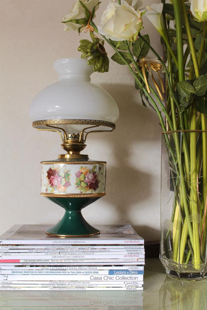 un angolo della mia casa con riviste impilate e una lampada antica